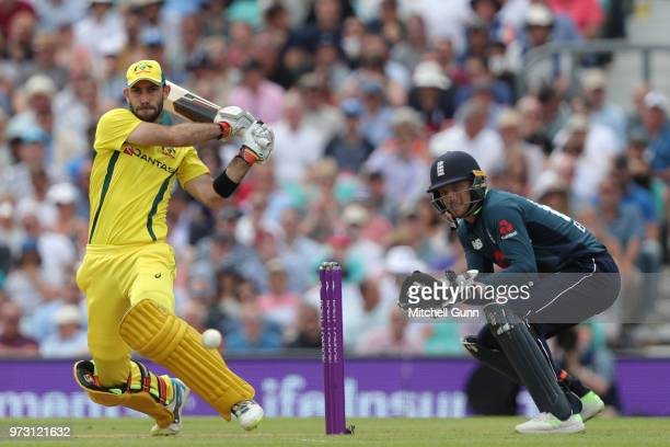 Glenn Maxwell of Australia hits the ball for four runs as Jos Buttler of England looks on during the 1st Royal London One day International match...