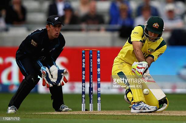 Glenn Maxwell of Australia plays a reverse sweep shot as Luke Ronchi of New Zealand looks on during the ICC Champions Trophy Group A match between...