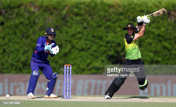 Glenn Maxwell of Australia plays a shot as Ishan Kishan of India looks on during the India and Australia warm Up Match prior to the ICC Men's T20...