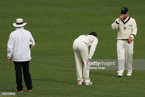 Glenn Maxwell of the Bushrangers grabs his right knee after bowling the ball during day one of the Sheffield Shield match between the Victoria...