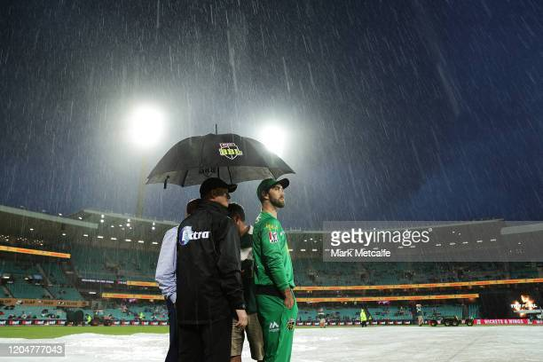 Glenn Maxwell of the Stars takes shelter under an umpire's umbrella during a rain delay before the Big Bash League Final match between the Sydney...