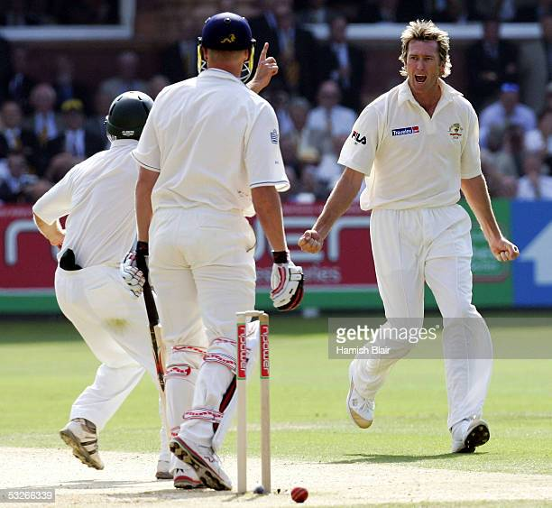 Glenn McGrath and Simon Katich of Australia celebrate the wicket of Andrew Flintoff of England during day one of the First Test between England and...