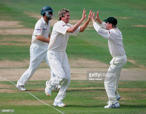 Glenn McGrath of Australia celebrates the wicket of Andrew Strauss of England with Michael Clarke during day one of the first npower Ashes Test match...