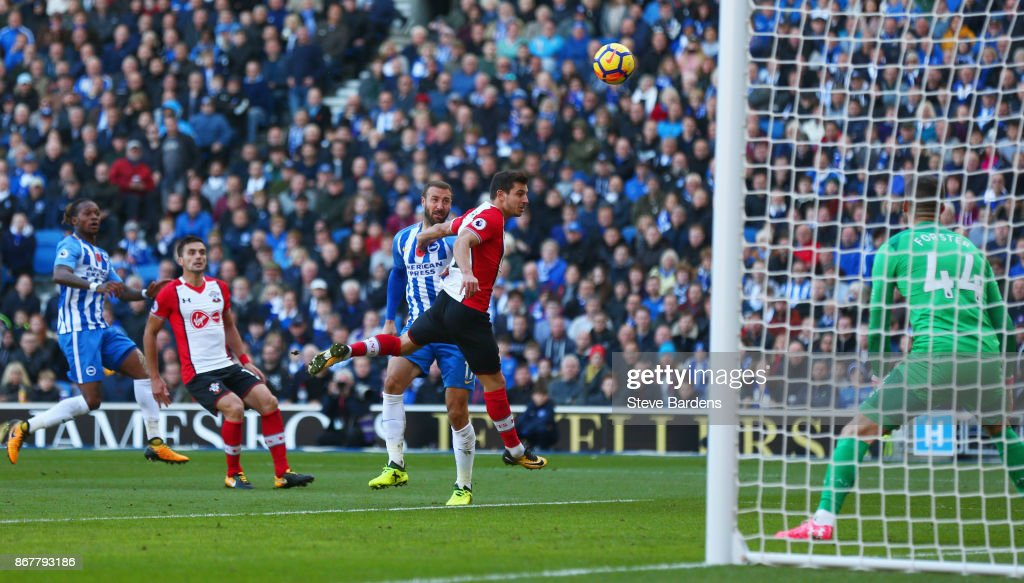 Glenn Murray of Brighton and Hove Albion (C) beats Cedric Soares of Southampton as he scores their first goal during the Premier League match between Brighton and Hove Albion and Southampton at Amex Stadium on October 29, 2017 in Brighton, England.