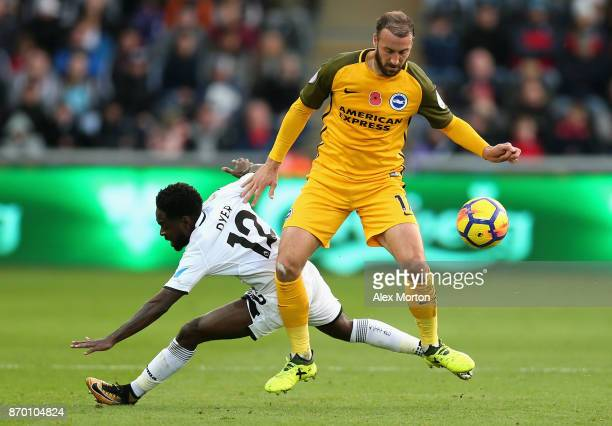 Glenn Murray of Brighton and Hove Albion is tackled by Nathan Dyer of Swansea City during the Premier League match between Swansea City and Brighton...