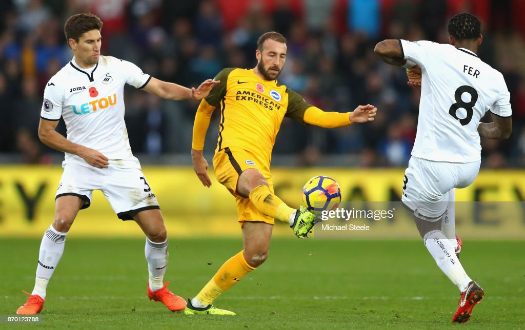 Glenn Murray (C) of Brighton and Hove Albion sheilds the ball from Federico Fernandez (L) and Leroy Fer (R) of Swansea City during the Premier League match between Swansea City and Brighton and Hove Albion at Liberty Stadium on November 4, 2017 in Swansea, Wales.