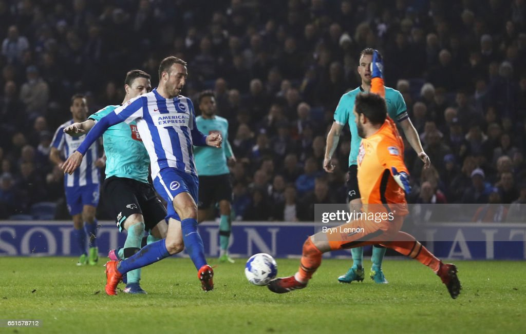 Glenn Murray of Brighton and Hove Albion shoots past goalkeeper Scott Carson of Derby County to score their third goal during the Sky Bet Championship match between Brighton & Hove Albion and Derby County at Amex Stadium on March 10, 2017 in Brighton, England.