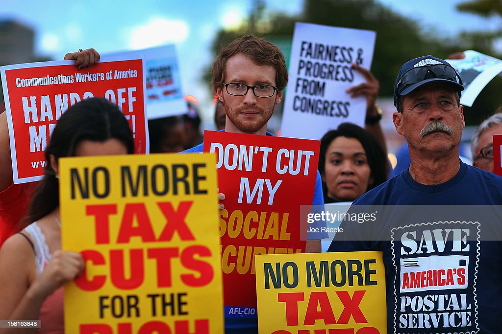 Glenn Rehn (C) and Sandy Lleo (R) along with other protesters rally together outside the office of U.S. Sen. Marco Rubio (R-FL) on December 10, 2012 in Doral, Florida. The protesters are hoping that Senators like Rubio will not cut medicare/social security benefits and will agree to raise taxes on the top 2% of earners in the country.
