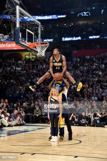 Glenn Robinson III of the Indiana Pacers dunks over a Pacers Dancer Pacers mascot Boomer and teammate Paul George during the Verizon Slam Dunk...