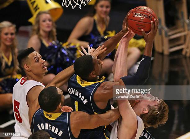 Glenn Robinson III of the Michigan Wolverines grabs a rebound as teammate Jon Horford hits Sam Dekker of the Wisconsin Badgers in the face while Ryan...