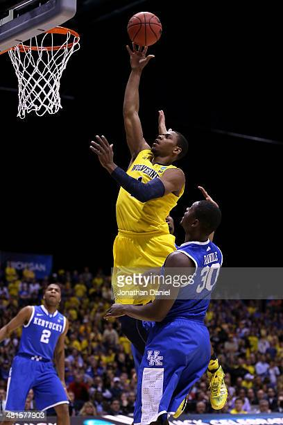 Glenn Robinson III of the Michigan Wolverines shoots the ball over Julius Randle of the Kentucky Wildcats in the first half of the midwest regional...