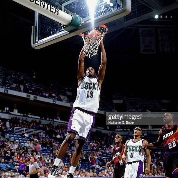 Glenn Robinson of the Milwaukee Bucks slam dunks against Cedric Ceballos the Phoenix Suns at The Bradley Center on November 29 1994 in Milwaukee...
