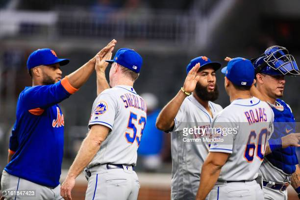 Glenn Sherlock Luis Rojas Wilson Ramos and Amed Rosario of the New York Mets shake hands following their 108 win over the Atlanta Braves at SunTrust...