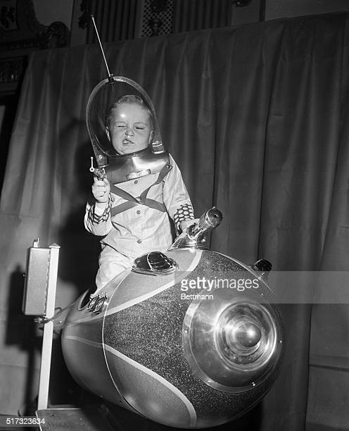 Glenn Sitterly four years old demonstrates his space suit and disintegrater pistol on a rocket ship ride at the American Toy Fair