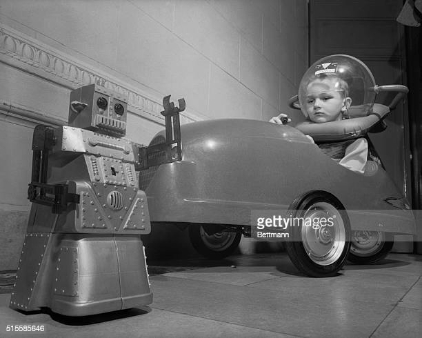 Glenn Sitterly sits in a fiberglass 'superjet car' and comtemplates 'Robit Robot' at the 51st American Toy Fair at the McAlpin Hotel in 1954