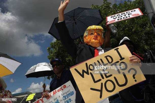 Glenn Terry dressed as President Donald Trump joins with other protesters at US Sen Marco Rubio's office on June 28 2017 in Doral Florida The...