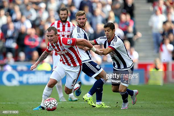 Glenn Whelan of Stoke City and Cristian Gamboa of West Bromwich Albion compete for the ball during the Barclays Premier League match between Stoke...