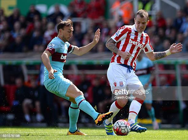Glenn Whelan of Stoke City and Mark Noble of West Ham United compete for the ball during the Barclays Premier League match between Stoke City and...