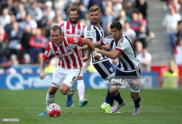 Glenn Whelan of Stoke City battles with Cristian Gamboa of West Bromwich Albion during the Barclays Premier League match between Stoke City and West...