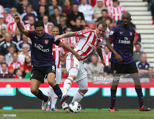Glenn Whelan of Stoke City is challenged by MIkel Arteta during the Barclays Premier League match between Stoke City and Arsenal at the Britannia...