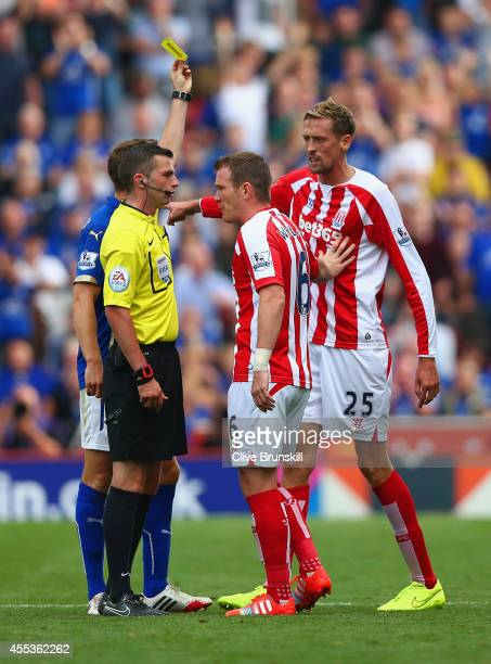 Glenn Whelan of Stoke City protests to Referee Michael Oliver as he shows Peter Crouch of Stoke City a yellow card during the Barclays Premier League...