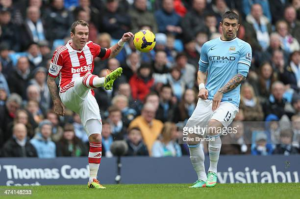 Glenn Whelan of Stoke City shoots past Aleksandar Kolarov of Manchester City during the Barclays Premier League match between Manchester City and...