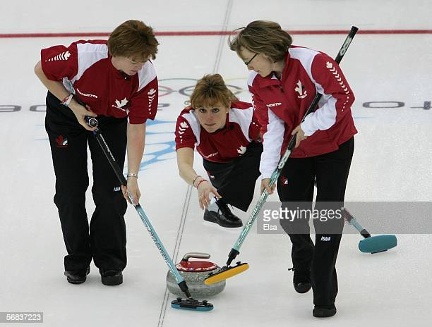 Glenys Bakker and Amy Nixon of Canada sweep after Christine Keshen delivered the stone on during the preliminary round of the women's curling between...