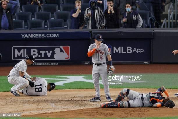 Gleyber Torres checks on Rougned Odor of the New York Yankees as Alex Bregman checks on Martin Maldonado of the Houston Astros after Odor and...