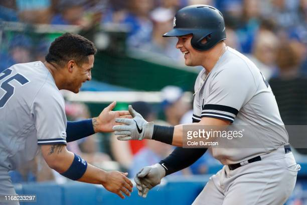 Gleyber Torres of the New York Yankees and Luke Voit celebrate Voit's home run in the sixth inning of their MLB game against the Toronto Blue Jays at...