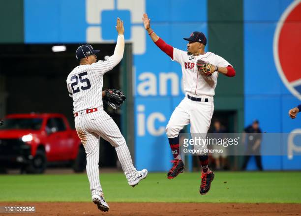 Gleyber Torres of the New York Yankees and the American League celebrates with Mookie Betts of the Boston Red Sox and the American League after...