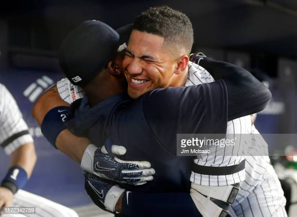 Gleyber Torres of the New York Yankees celebrates his fourth inning home run against the Texas Rangers with teammate Cameron Maybin at Yankee Stadium...