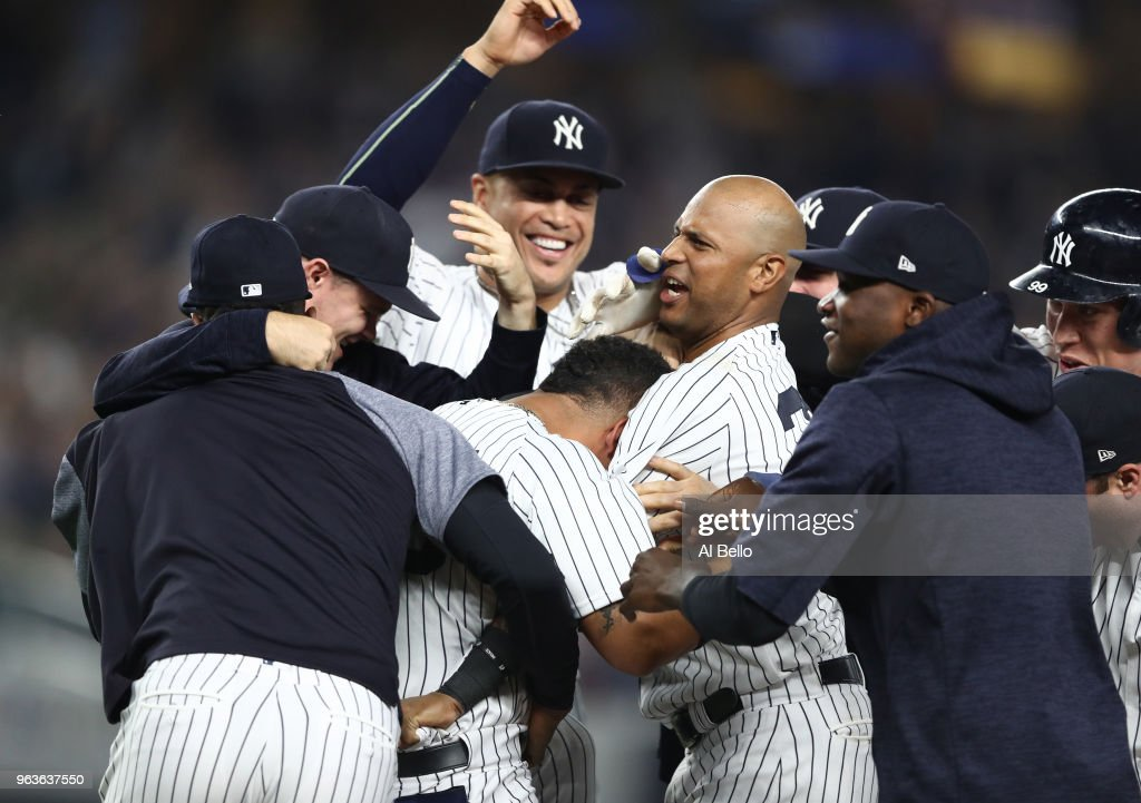 Gleyber Torres #25 of the New York Yankees celebrates with his teamates after hitting a game winning RBI single in the tenth inning against the Houston Astros at Yankee Stadium on May 29, 2018 in New York City.