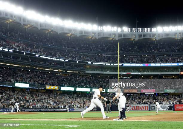Gleyber Torres of the New York Yankees is congratulated by first base coach Reggie Willits after Torres hit a three run home run off pitcher Josh...