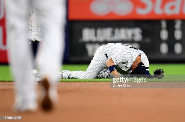 Gleyber Torres of the New York Yankees lays on the ground during the fourth inning of their game against the Toronto Blue Jays at Yankee Stadium on...