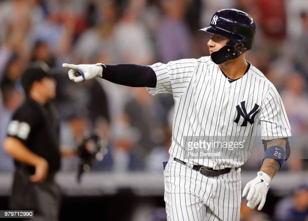 Gleyber Torres of the New York Yankees runs up the first base line pointing to his teammates in the dugout as he runs out his three run home run in...