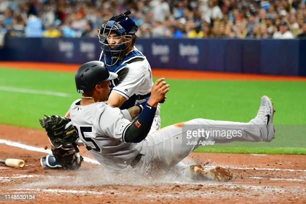 Gleyber Torres of the New York Yankees slides past Travis d'Arnaud of the Tampa Bay Rays to score in the fifth inning at Tropicana Field on May 11...