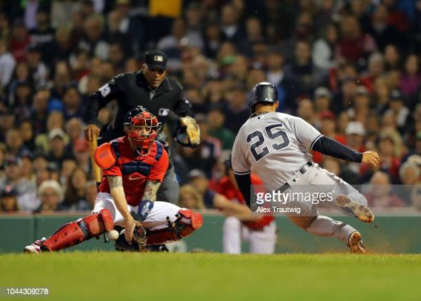 Gleyber Torres of the New York Yankees slides safely into home against Blake Swihart of the Boston Red Sox during the game at Fenway Park on Friday...