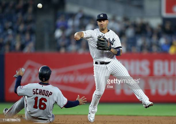 Gleyber Torres of the New York Yankees turns the double play as Jonathan Schoop of the Minnesota Twins is out at second in the second inning at...
