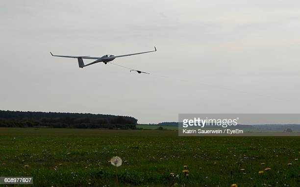 glider flying over green field against sky - glider - fotografias e filmes do acervo