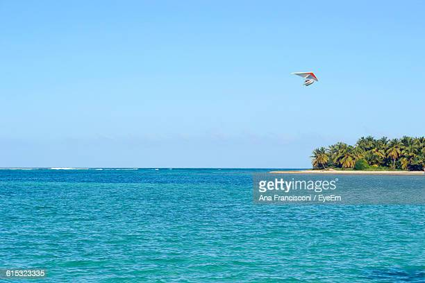 Glider Flying Over Sea Against Clear Sky