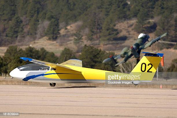 A TG-10B glider lifts into the air as it is towed down the runway by a Piper Super Cub tow plane at the U.S. Air Force Academy, Colorado.