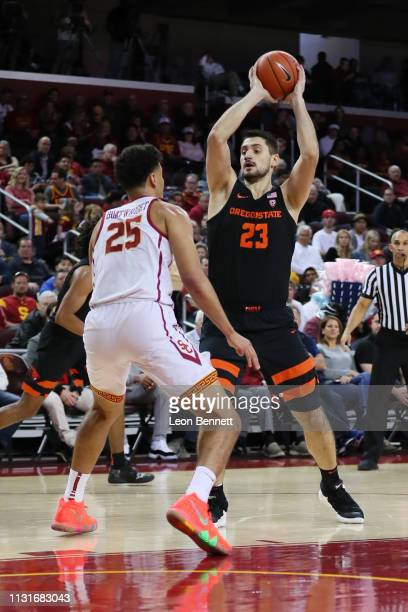 Gligorije Rakocevic of the Oregon State Beavers handles the ball against Bennie Boatwright of the USC Trojans during a college basketball game at...