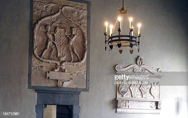 Glimpse of living room with a marble plaque depicting the coat of arms of Pistoia held by a pair of winged genii above the door from Andrea del...