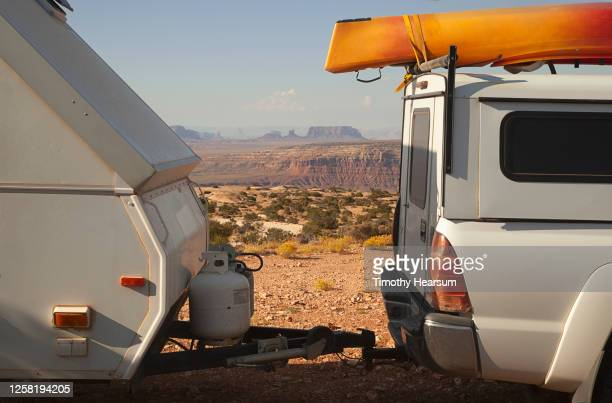 glimpse of monument valley between a pick-up truck and travel trailer at muley point on cedar mesa - timothy hearsum imagens e fotografias de stock