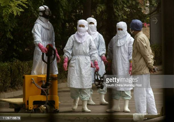 Glimpse through security fence showing a group of medical staff from the Sino-Japanese hospital, with gas masks and suits to protect against SARS, as...
