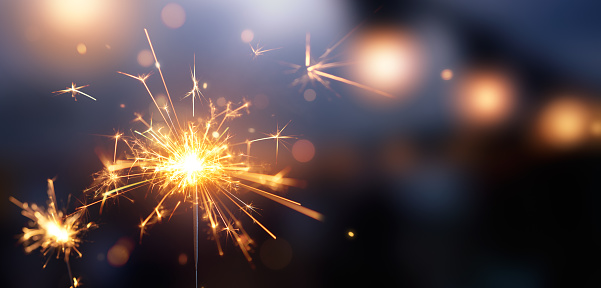 Glittering burning sparkler against blurred bokeh light background 1171665644