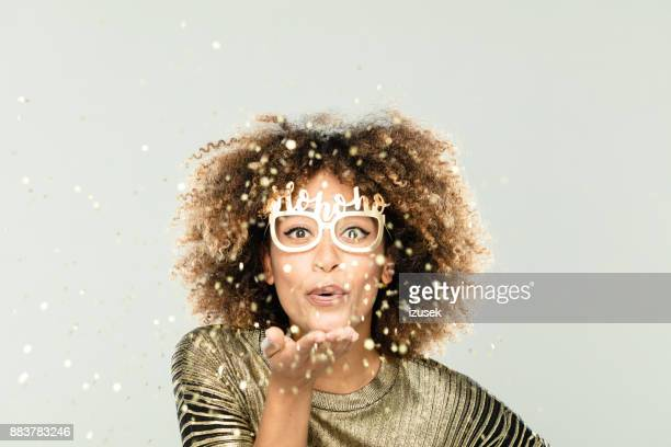 Glittering christmas portrait of beautiful young woman in gold sparkles