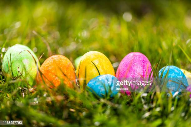 glittering easter eggs in meadow - easter religious background stock pictures, royalty-free photos & images
