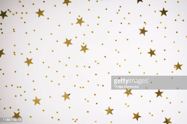 glittering golden stars on white background - tinsel stock pictures, royalty-free photos & images
