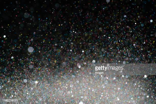 glittering small decoration plastic debris with colorful powder flour flying in mid air - glinsterend stockfoto's en -beelden